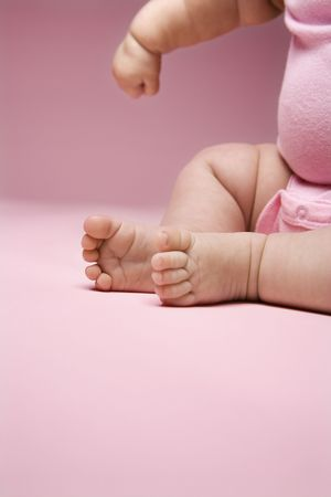babys: Close up of Asian babys legs and feet and arm.