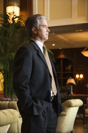 prime adult: Caucasian prime adult male businessman standing in hotel lobby.