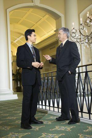 prime adult: Caucasian prime adult male businessman and Asian prime adult male businessman in hotel.