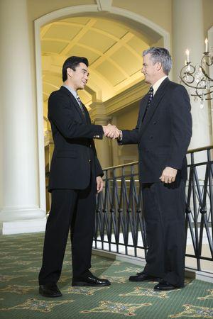 prime: Caucasian prime adult male businessman and Asian prime adult male businessman in hotel.