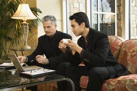 prime adult: Prime adult Asian and Caucasian businessmen. Stock Photo