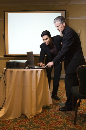Asian prime adult businessman helping prime adult Caucasian businessman give presentation. Stock Photo - 2376358