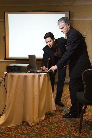 technolgy: Asian prime adult businessman helping prime adult Caucasian businessman give presentation.