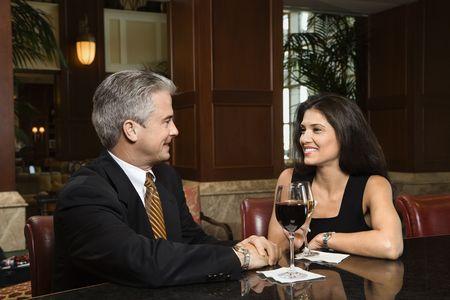 prime adult: Prime adult Hispanic female and Caucasian prime adult male sitting at bar talking. Stock Photo