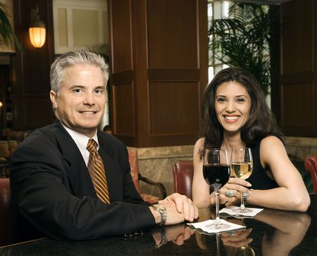 prime adult: Prime adult Hispanic female and Caucasian prime adult male sitting at bar looking at viewer smiling.