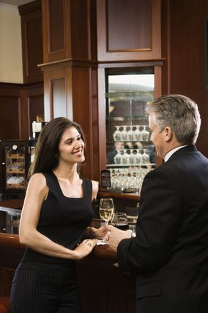 prime adult: Prime adult Hispanic female and Caucasian prime adult male standing at bar talking. Stock Photo