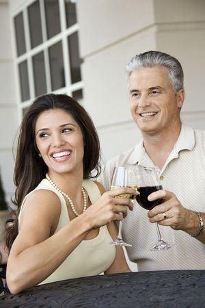 prime adult: Prime adult Hispanic female and Caucasian prime adult male toasting sitting at table.