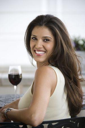 prime adult: Prime adult Hispanic female sitting at table. Stock Photo
