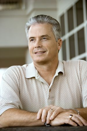 prime adult: Caucasian prime adult male sitting at table. Stock Photo