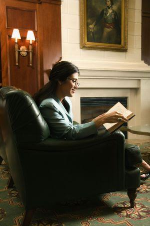 prime adult: Prime adult Hispanic female sitting and reading. Stock Photo