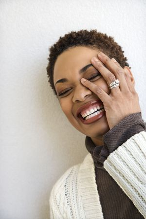 close up   head: Close up head and shoulder of African-American woman standing against white wall smiling with hand on face and eyes closed.