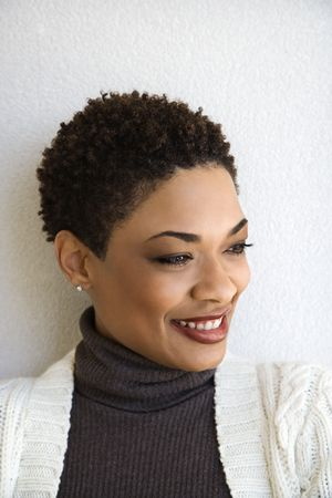 close up   head: Close up head and shoulder of African-American woman standing against white wall smiling with head turned to side.