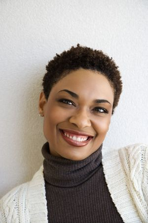 woman looking up: Close up head and shoulder of African- American woman standing against white wall smiling looking at viewer. Stock Photo