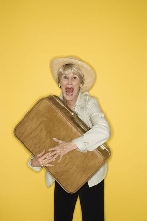clutching: Caucasian mature adult female grasping suitcase.