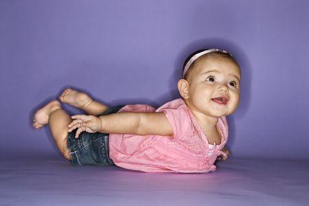 females only: Hispanic female baby lying on stomach.