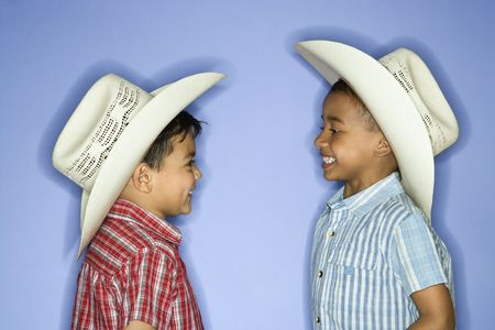 eachother: Hispanic and African American male child in cowboy hats.