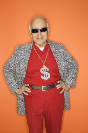 70s adult: Mature adult Caucasian male wearing money sign necklace.