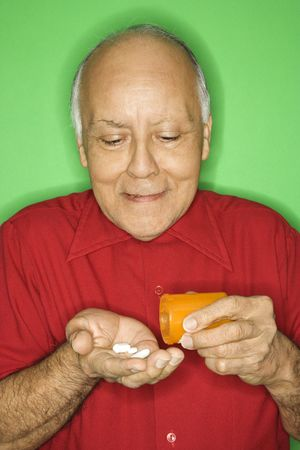 Mature adult Caucasian male emptying pill bottle into hand. Stock Photo - 2376522