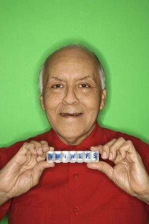 Mature adult Caucasian male holding pill organizer. Stock Photo - 2376468