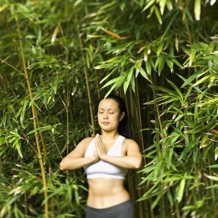 Half length portrait of Asian American woman in fitness attire standing in yoga position in bamboo forest in Maui, Hawaii. Stock Photo - 2555119