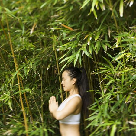 holistic view: Half length portrait of Asian American woman in fitness attire standing in yoga position in bamboo forest in Maui, Hawaii.