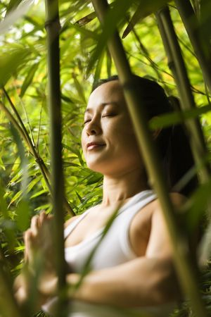holistic view: Portrait of Asian American woman in fitness attire standing in yoga position with eyes closed in bamboo forest in Maui, Hawaii.