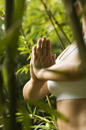 Portrait of Asian American woman in fitness attire standing in yoga position in bamboo forest in Maui, Hawaii.