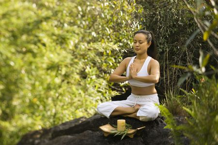 Asian woman sitting on boulder in forest meditating in Maui, Hawaii. Stock Photo - 2555866