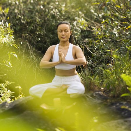 Asian American woman sitting on boulder in forest meditating with candle in Maui, Hawaii. Stock Photo - 2555116