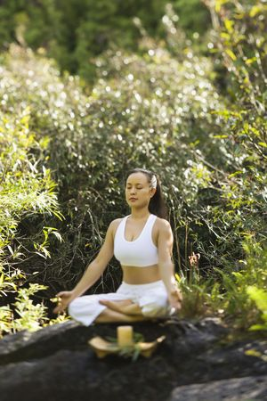 Asian American woman sitting on boulder in forest meditating with candle in Maui, Hawaii. Stock Photo - 2555138