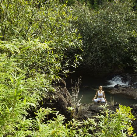 Asian woman sitting on boulder by creek meditating in Maui, Hawaii. Stock Photo - 2556054