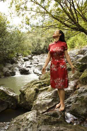 Asian woman in kimono standing on rock by creek in Maui, Hawaii. photo