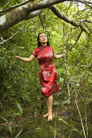 Portrait of Asian American woman in ethnic attire standing on rock in bamboo in Maui, Hawaii. photo