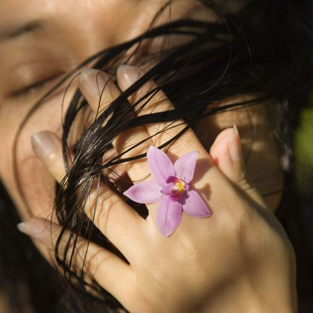 Mid-adult Asian female holding flower up to her face. photo