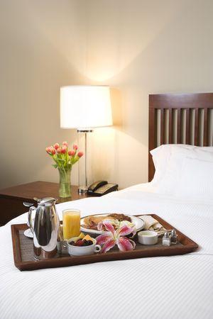 Bandeja del desayuno que pone en la cama blanca en hotel del upscale.