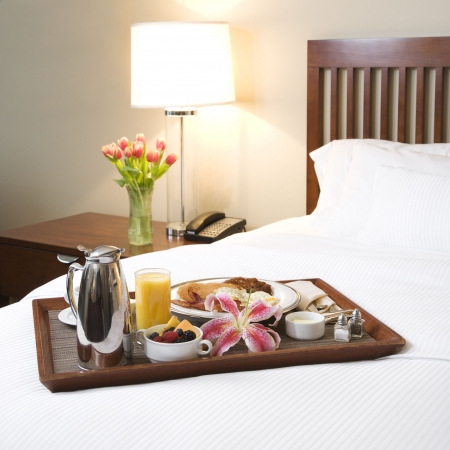 Breakfast tray laying on white bed in upscale hotel. Stock Photo