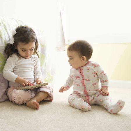 bambini seduti: Bambini caucasici ragazza seduta sul pavimento camera da letto guardando libro.