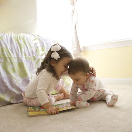 Caucasian girl children sitting on bedroom floor looking at book. photo