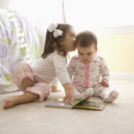 Caucasian female children sitting on bedroom floor looking at book. photo