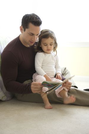 Caucasian father reading book to girl on lap sitting on floor. Stock Photo - 2555375