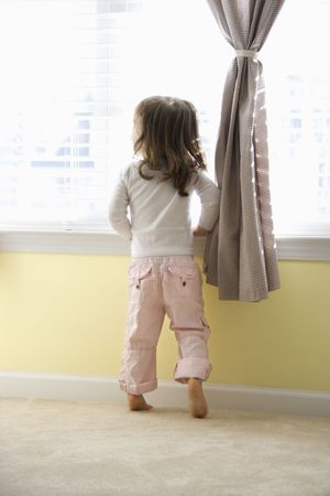 anticipating: Caucasian girl toddler standing on tip toes looking out of window.