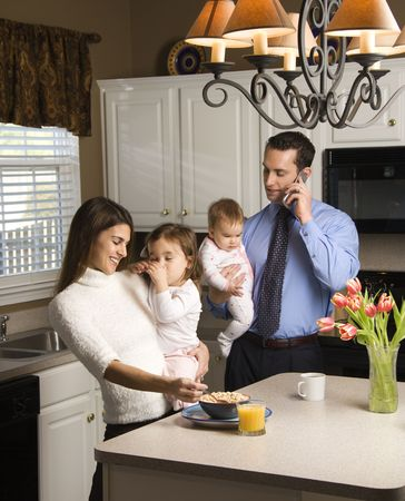 Caucasian mother and father in kitchen busy with children and cellphone. Stock Photo - 2555145