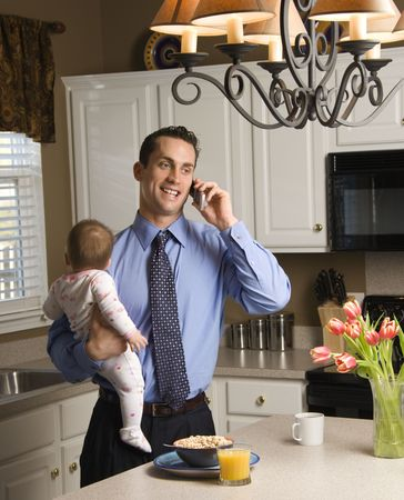 Caucasian father in suit holding baby  and talking on cellphone in kitchen.