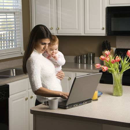 Caucasian woman holding baby  and typing on laptop computer in kitchen.