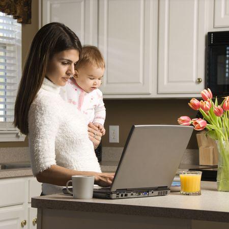pagando: Madre y beb� celebraci�n de mecanograf�a en ordenador port�til en la cocina.