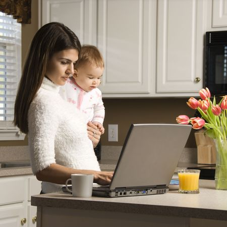 paying: Mother holding baby  and typing on laptop computer in kitchen.