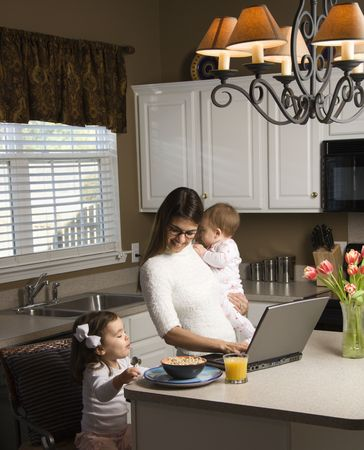 Caucasian mother holding baby  and typing on laptop computer with girl eating breakfast in kitchen. photo