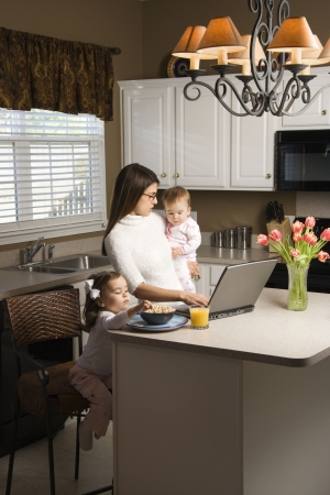 working mother: Caucasian mother holding baby  and typing on laptop computer with girl eating breakfast in kitchen.