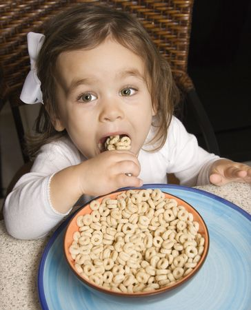 Caucasian girl eating bowl of cereal.
