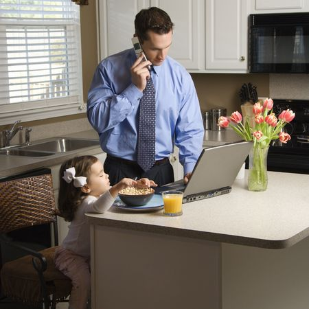 Father in suit on cellphone and laptop while daughter eats breakfast. Stock Photo - 2555931